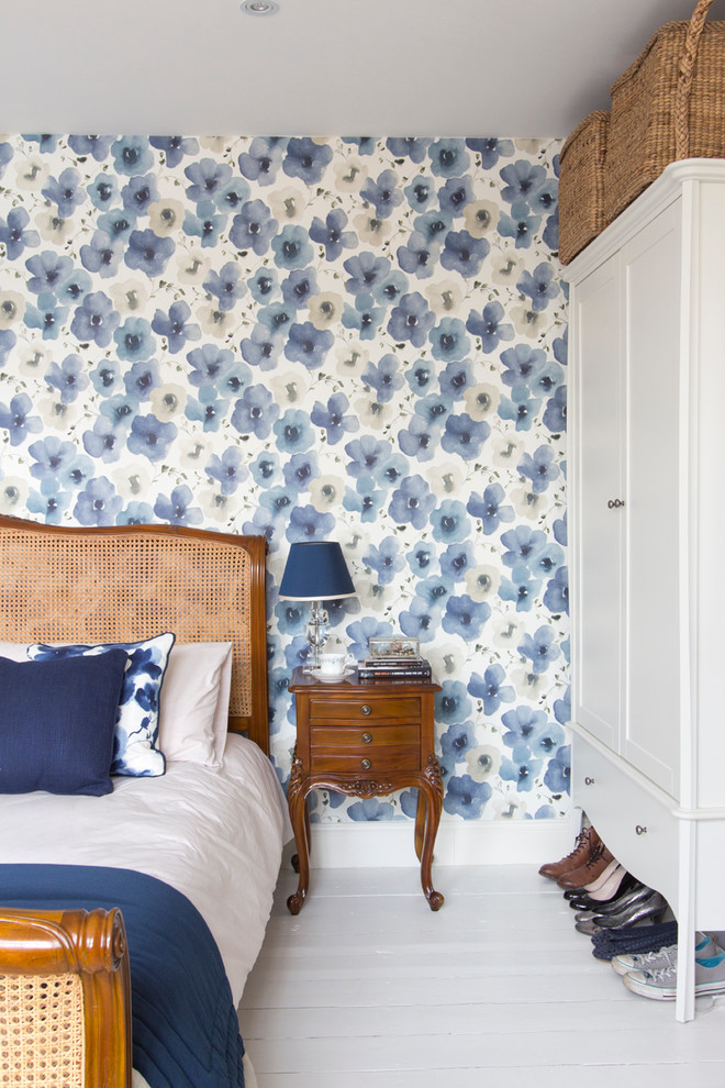 bedroom with white floor, white cupboard, white blue linen bed, wooden bedding with rattan accent, blue flowers wallpaper