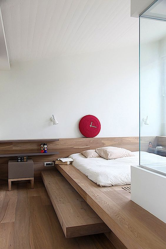 bedroom with wooden flooring, built in bedding, white linene bed, red clock