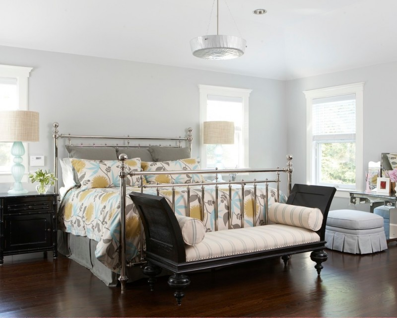 bedroom with wooden flooring, makeup glass table round cushions, black wooden small cupboard, flowery linen