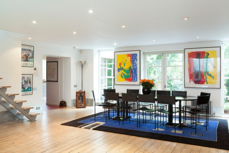 black dining table modern black dining chairs blue and black area rug colorful artworks white walls glass window glass doors