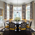 Black Dining Table Pedestal Table Black Area Rug Black Chairs Yellow Patterned Curtains Glass Windows Glass Doors Colorful Patterned Curtains Shade