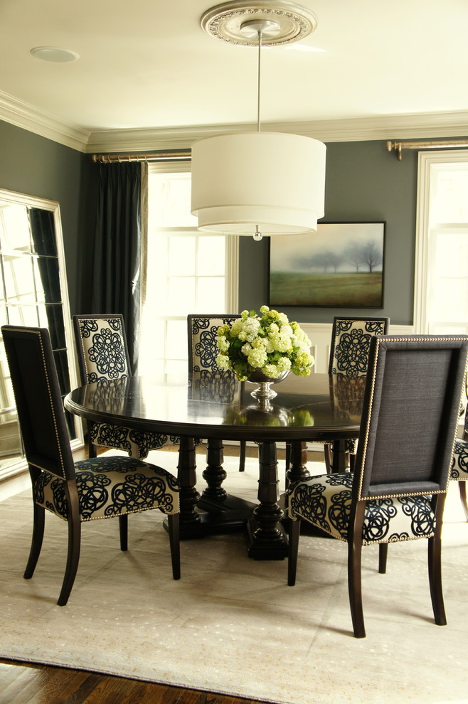 black dining table wooden chairs with patterned cushions white chandelier beige area rug artwork dark blue curtains white framed glass windows