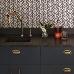 Black Sink With Golden Faucet, Black Cabinet With Golden Handles, Black Marble Top, Brown Patterned Backsplash