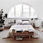 Boho Bedroom With Wooden Floor, Rattan Rug, White Paited Wall, Bed On The Floor Near A Half Circle Windows, Light Grey Bedlinen, Plants, Minimalist Table With Lamp