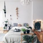 Boho Bedroom With Wooden Floor, White Bed Linen With Grey Accent, White Painted Wall, Hanged Plants, Plants On The Floor