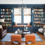 Bookcase With Ladder And Rail Blue And White Patterned Area Rug Orange Stools Brown Sofa Beige Armchairs Window Seat Chandelier Coffee Table