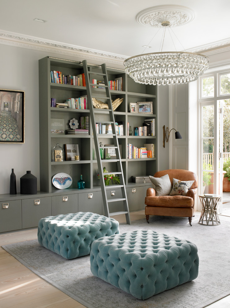 bookcase with ladder and rail crystal chandelier blue tufted ottoman brown armchair side table grey area rug vintage cabinet wall scone glass doors