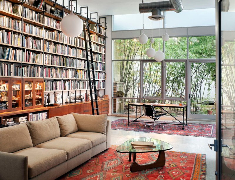 bookcase with ladder and rail red patterned area rugs pendant lights noguchi coffee table beige sofa office chair and desk glass windows