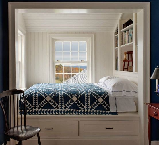 built in bed in the side of the window with white wooden bedding, shelves inside, storage under