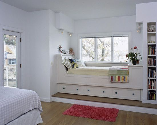 built in bed near the window sill with white wooden bedding, white cushion, colorful pillows, storage under, bookshelves ath the foot of the bed