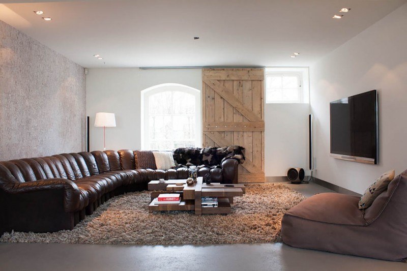 classic leather sofa barn door grey shag area rug wooden coffee table bean bag white walls windows table lamp
