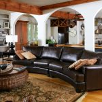 Classic Leather Sofa Curved Sofa Throw Pillows Rattan Coffee Table Wooden Top Tray Black Iron Armchair Patterned Rug Wooden Floor