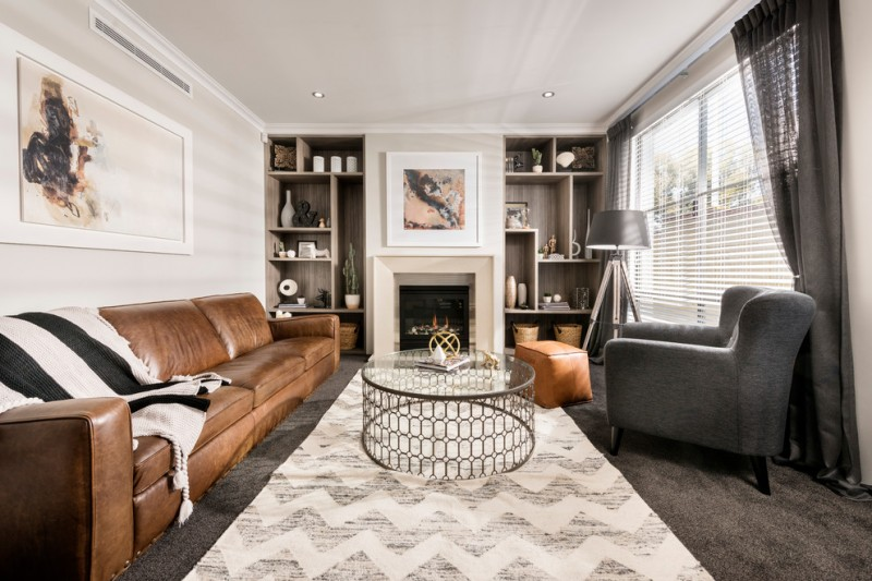 classic leather sofa glass coffee table chevron area rug throw blanket grey armchair floor lamp built in shelves fireplace curtain stool