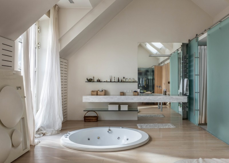contemporary bathroom with wooden pattern marble floor, teal colored wall, white wall, large mirror near marble table, round white sunken tub