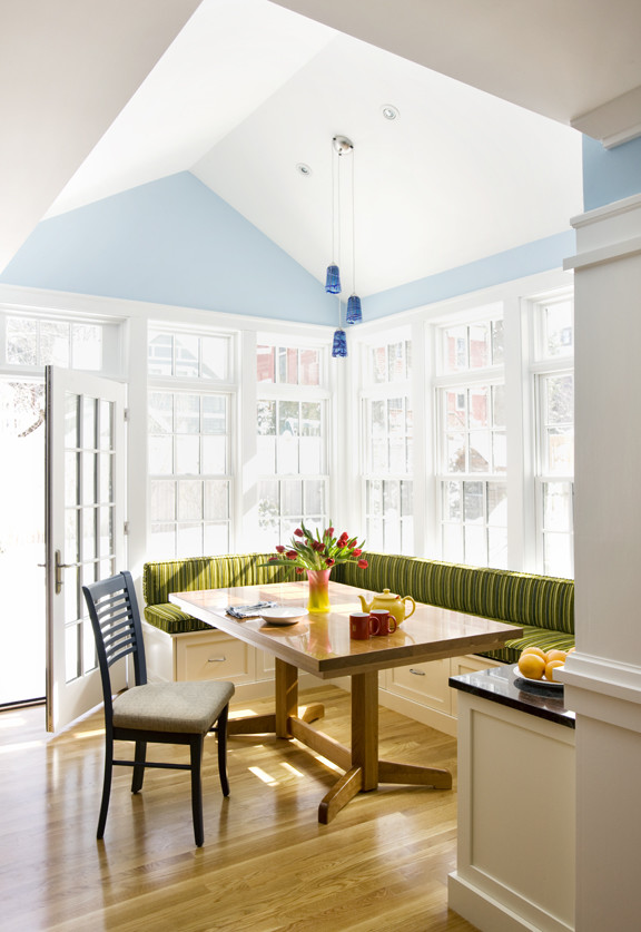 corner bench seating with storage green striped seat cushions drawers wooden table black chair blue walls blue pendant lamps glass windows