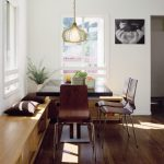 Corner Bench Seating With Storage Pendant Lamp Black Square Pedestal Table Brown Chairs Brown Throw Pillows White Walls Glass Windows Shelves Drawers