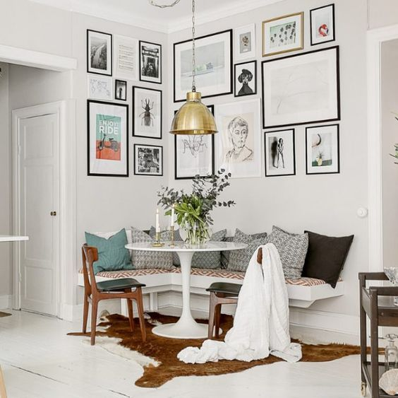 corner dining set with white round table, wooden chairs, white corner bench with white red cushion and grey pillows