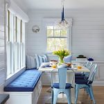 Corner Dining Set With White Wooden Table, Blue Metallic Chairs, White Corner Bench With Blue Cushion, Blue Pillows, Chandelier