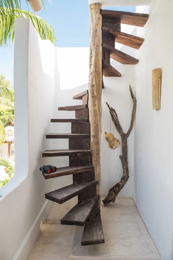 dark wooden stairs circled with lighter wooden support, without handrails in small space with white wall