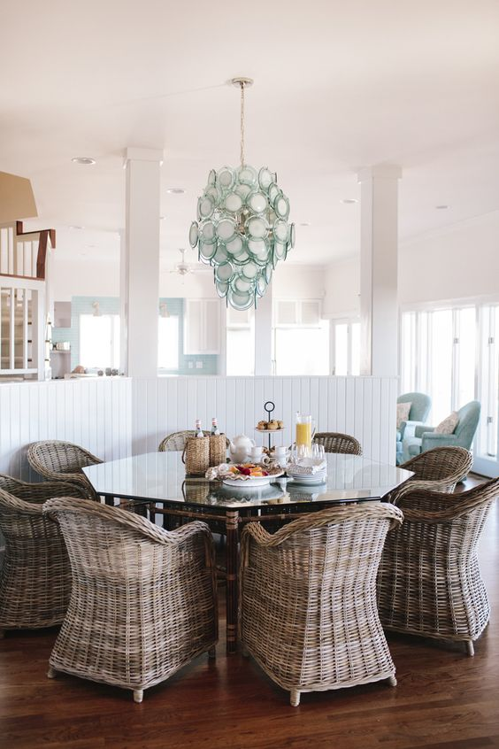 dining area with wooden floor, rattan chairs octagonal table with glass top, blue glass chandelier, white half wall partition,
