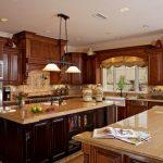 Double Pendant Light Brown Cabinets Brown Island Beige Granite Countertops Stove Beige Backsplash Windows Sink Oven