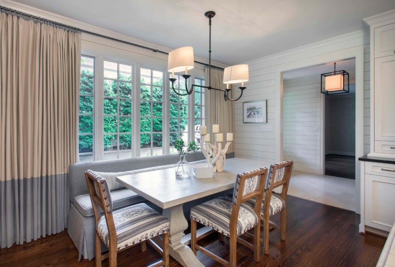 double pendant light grey bench with back cushion windows white table wooden chairs with patterned cushions beige grey curtains wooden floor