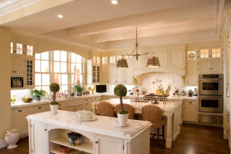 double pendant light white double island white backsplash tile beige cabinets stove range hood barstools oven sink windows