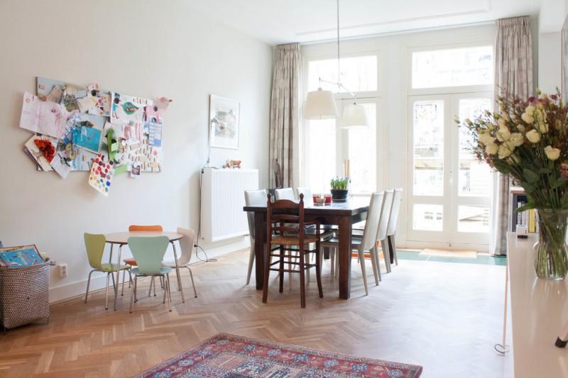 double pendant light wooden dining table white chairs colorful rug herringbone floor curtains white glass doors bookshelves