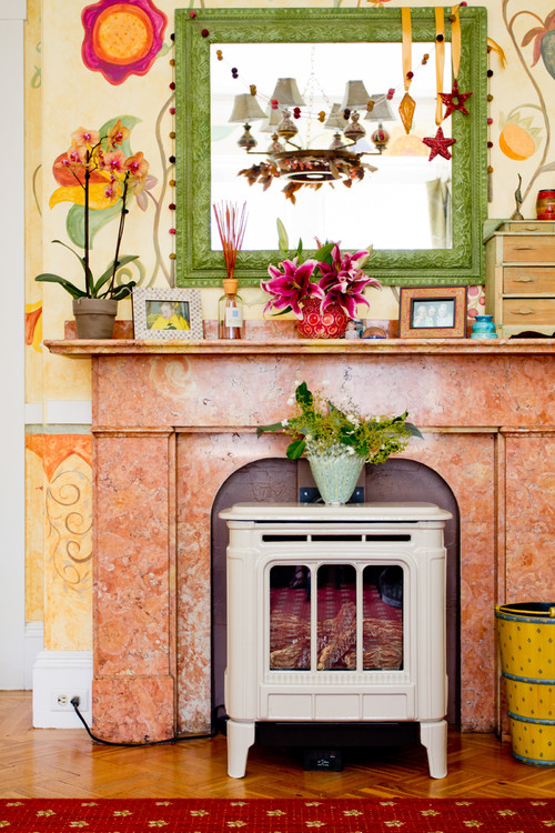 eclectic room with plants patterned wallpaper, fireplace, small cabinet, terracota floor