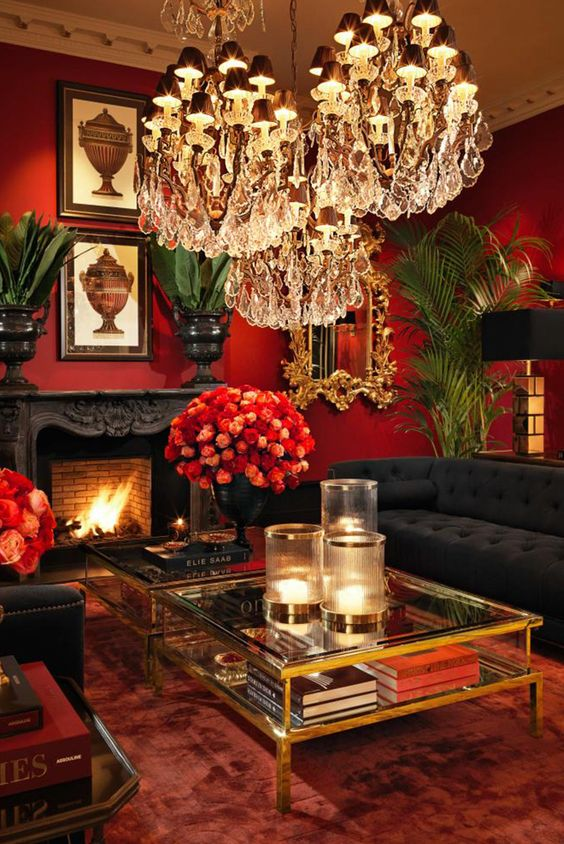 elegant living rom with red wall, red rug, black sofas, red roses in black vases, diamond chandelier, plants, clear glass coffee table