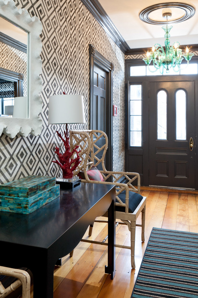 entry hallway with brown wooden floor, striped rug, black wooden table with white wooden chair, mirror, lamp, blue chandelier, brown geometric wallpaper