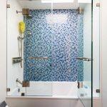 Frameless Hinged Tub Door Blue Mosaic Wall Tile Shower Head Built In Tub Blue Bathroom Mat White Walls Brown Floor