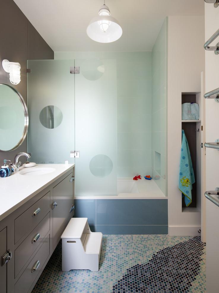 frameless hinged tub door built in tub mosaic floor tile towel holder grey vanity white top white sink faucet wall sconce wall mirror shelves