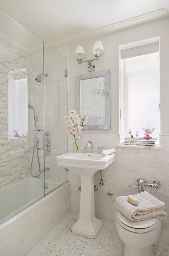 frameless hinged tub door built in tub white freestanding sink mosaic floor and wall tiles window mirror wall sconce shower head