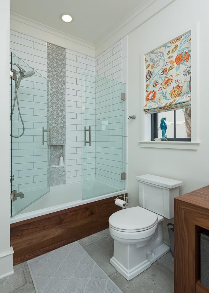 frameless hinged tub door white subway wall tile wooden vanity patterned window shade grey floor tile bathroom mat shower head