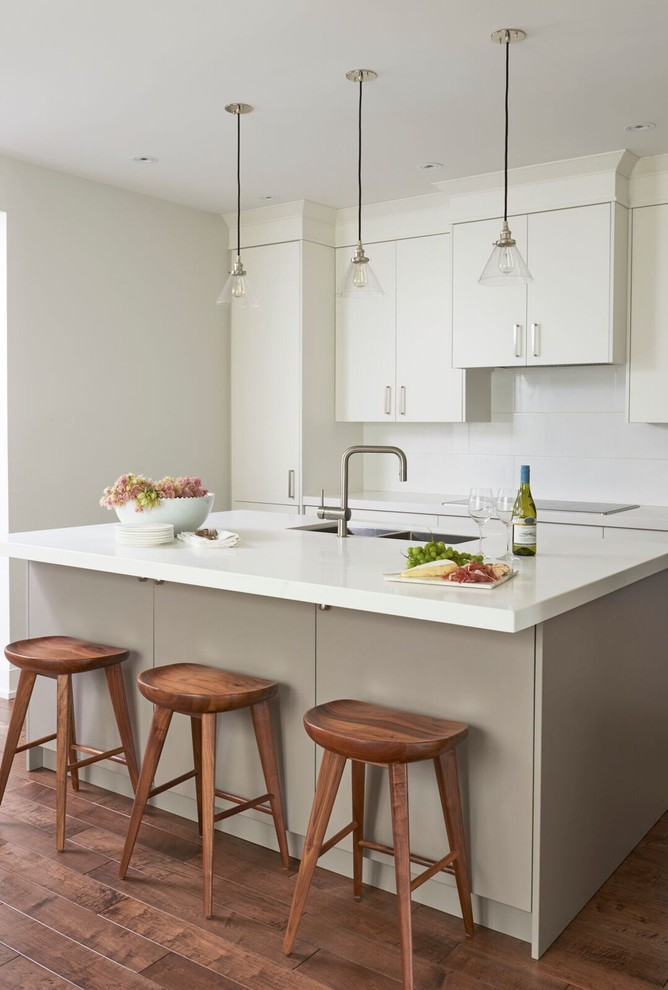 glass dome pendant light white flat panel kitchen cabinets beige island wooden stools wooden floor white countertop stovetop backsplash