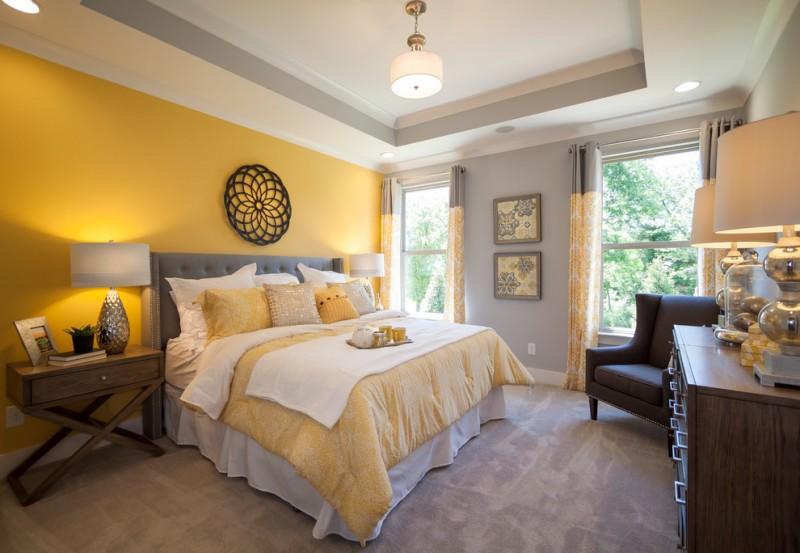 grey yellow bedroom grey bed tufted headboard wooden nightstands artworks wooden drawers table lamps windows pendant lamp