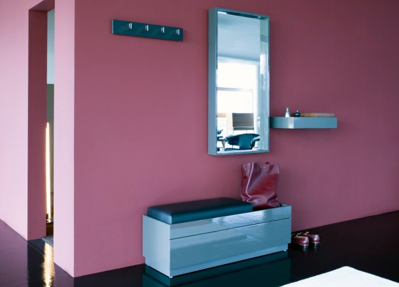 hallway with back floor, purple painted wall, silver bench with storage and black cushion, metallic framed mirror, metallic shelf