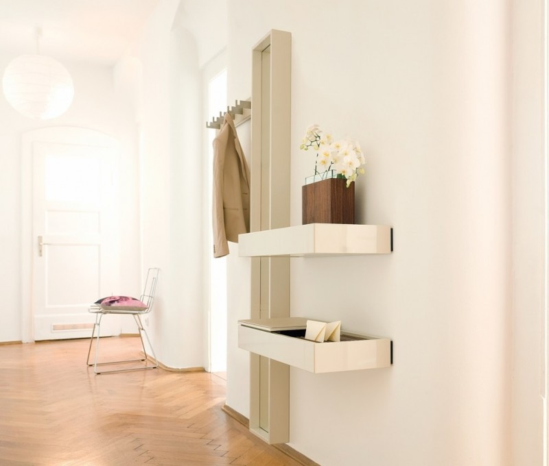 hallway with wooden floor, white painted wall, coat racks, shelves, tall mirror