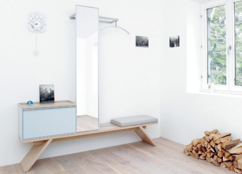hallway with wooden floor, white painted wall, white framed windows, wooden bench with storage box, tall mirror, place to hang clothes
