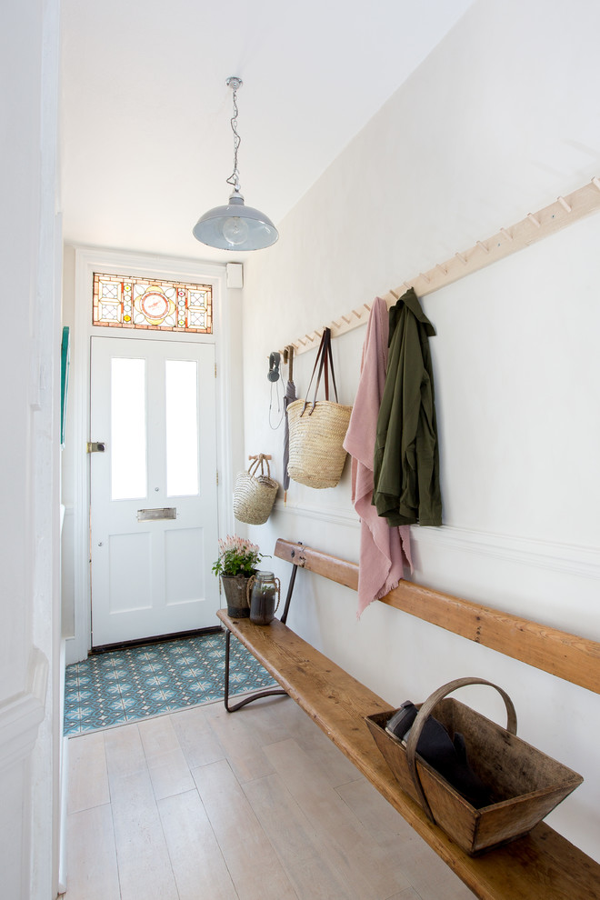 hallways with white painted wall, cremme colored floor, long wooden bench, hanging racks along the bench