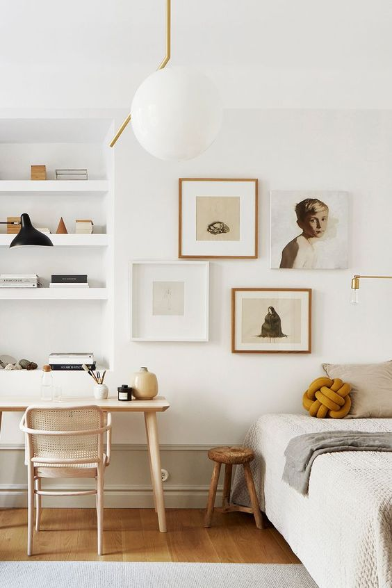 home office in bedroom with wooden floor, white wall, white wooden shelves, nude wooden table and chair, wooden stool, ball hanging lamp