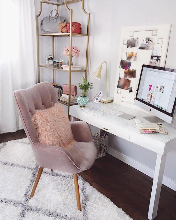 home office with dark wooden floor, white rug, white wooden table, pink velvet chair, golden metal shelves