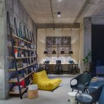 Home Office With Grey Floor, Blue Rug, Blue Plastic Chairs, Yellow Bean Bag, Wooden Shelves, Wooden Table, Hanging Lamp