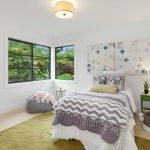 Kids Bedroom With White Wall, Peach Flooring With Green Rug, White Bed, Grey Ottoman, Grey Blanket, Green Side Table