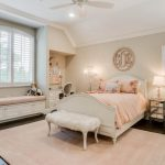 Kids Bedroom With Wooden Flooring, Soft Peach Rug, White Bedding, White Fur Bench, White Built In Shelves, Window Nook, And Study Area, Table Lamps, Fan
