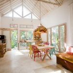 Kitchen Dining Room With Wooden Square Table, Colorful Chairs, Rattan Chandelier With Fruit, Wooden Kithecenette, Bamboo Racks, Bamboo Couch