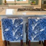 Kitchen In White With White Marble Top Island And Blue Coconut Leaves Patterned Chairs