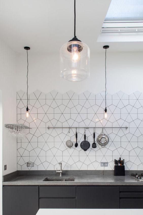 kitchen with black cabinet, grey marble top, white hexagonal backsplash, hanging lamp, hanging rail