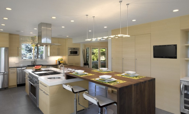 kitchen with mostly in with brown cabinet, long wooden island with island pendant